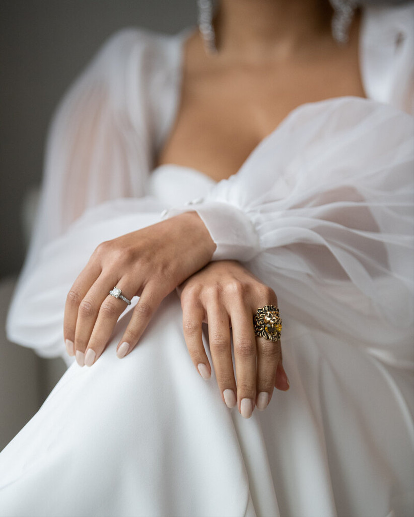 Black bride sits with hands crossed in her lap nails are painted elegant ivory shade