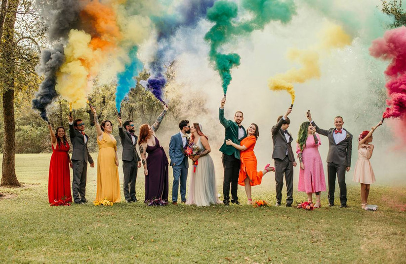 bride and groom kiss as their wedding party stands on either side holding colorful smoke bombs