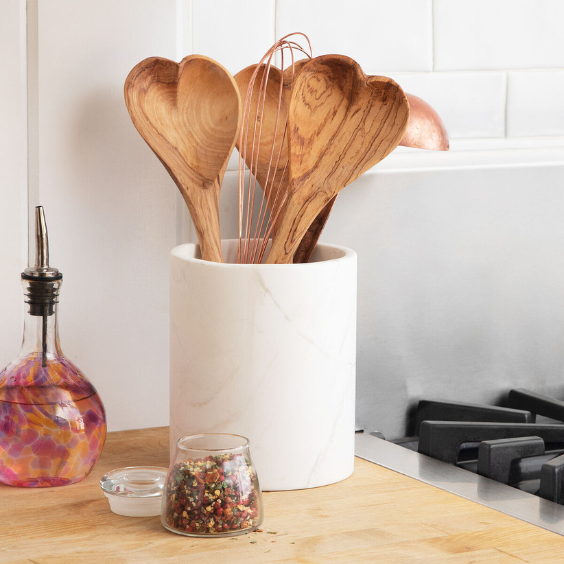 White utensil holder on kitchen counter with heart-shaped serving spoons