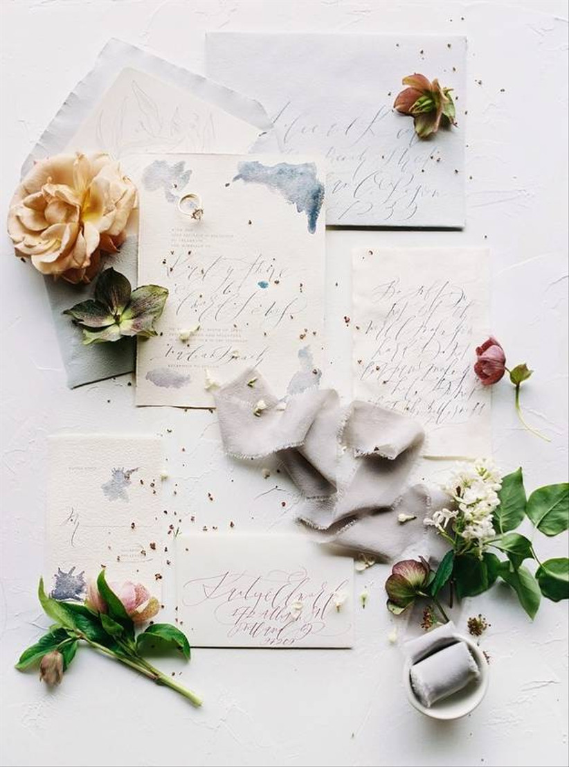 wedding flat lay with silk ribbon, flowers and watercolor invitations