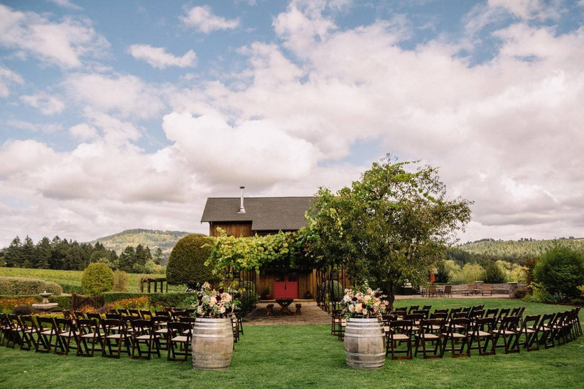 outdoor wedding ceremony overlooking vineyards and barn with vine-covered arbor in front