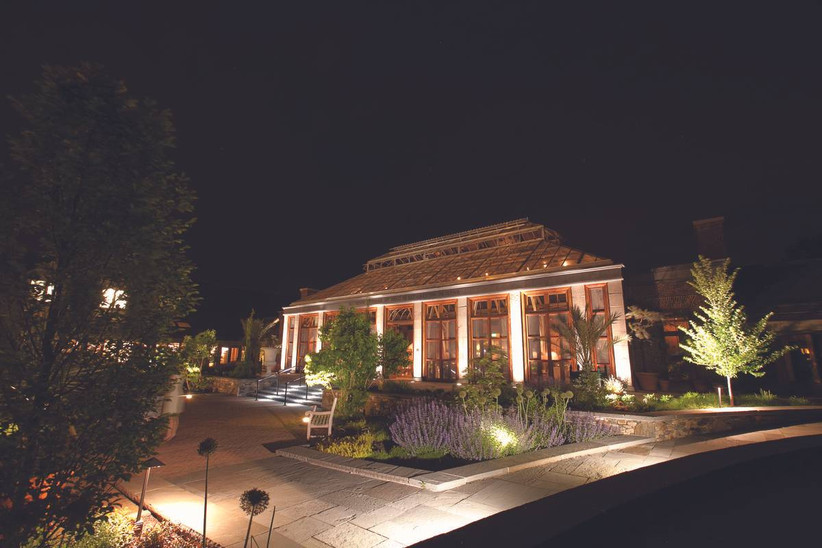 exterior of botanical garden wedding venue at night building is lit up at the front with landscaped garden beds on both sides