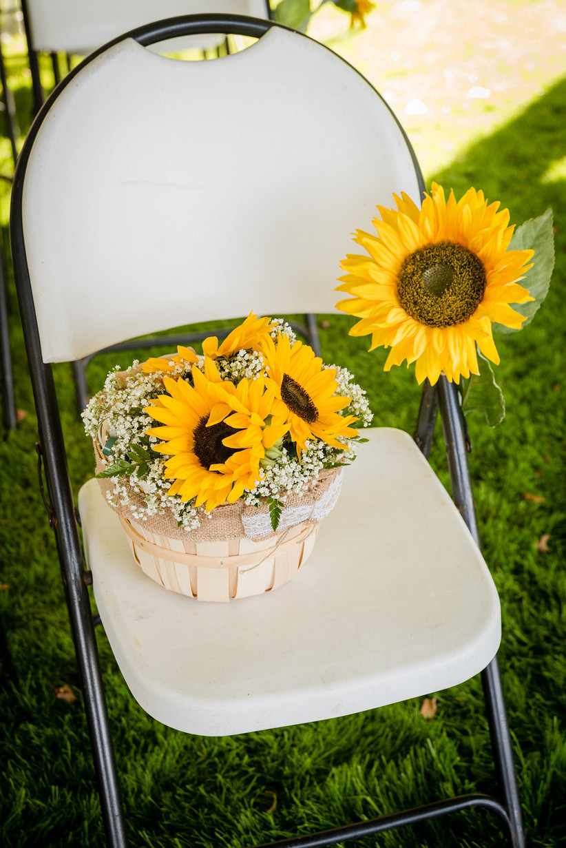 folding chair on grass at outdoor wedding ceremony with a basket of yellow sunflowers and baby's breath