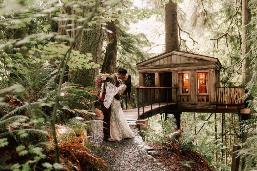 wedding couple kissing next to treehouse