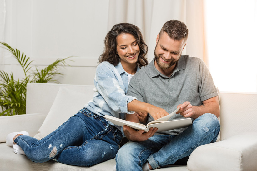 Couple snuggled up together on couch looking at photo album