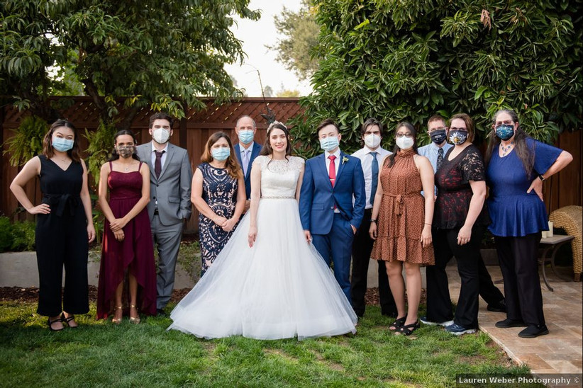 bride and groom stand with family members wearing masks at outdoor wedding venue