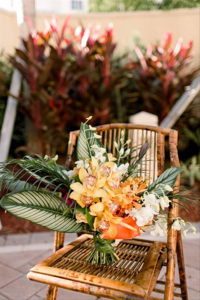 tropical colorful beach wedding bouquet with orange cymbidium orchids and palm fronds