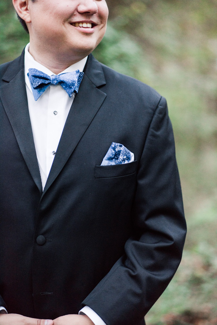 close-up of black tuxedo and blue pocket square decorated with galaxy star pattern