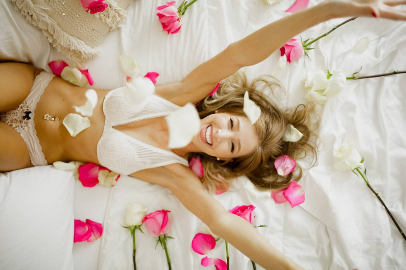 cute boudoir session idea smiling bride lays on a bed and tosses rose petals into the air