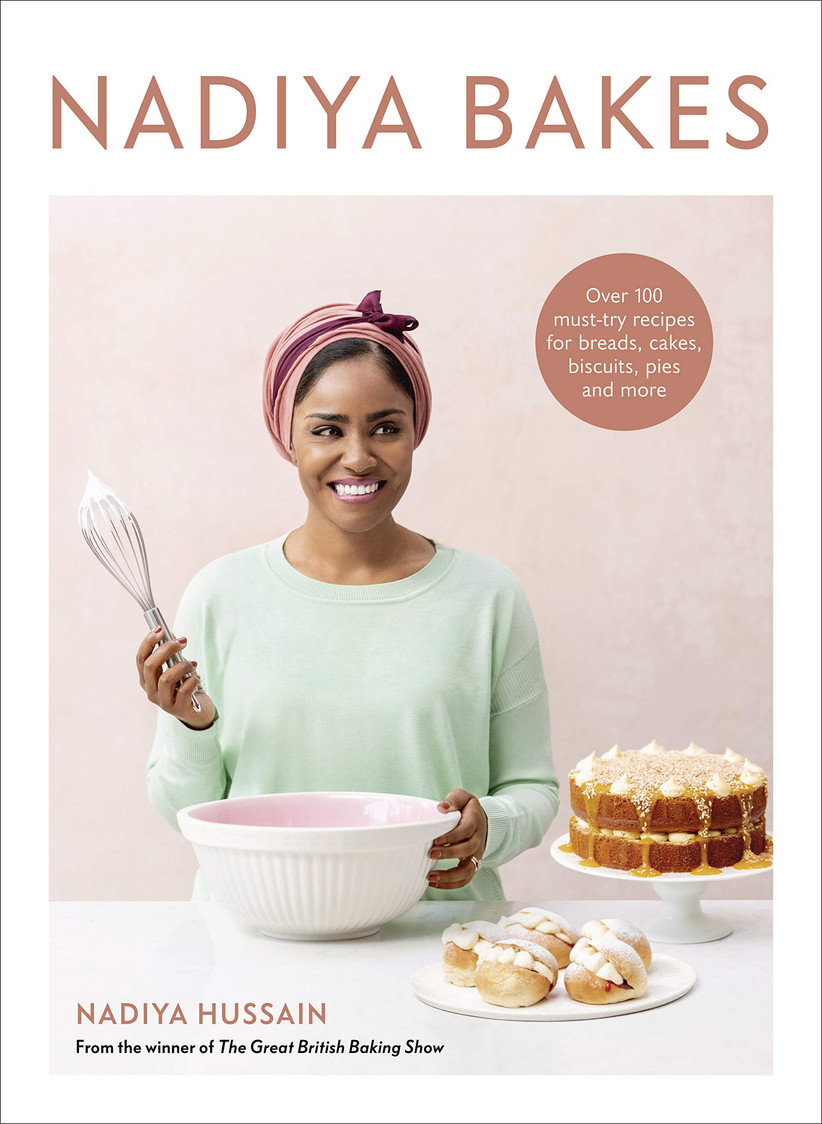 Nadiya Bakes recipe book cover with picture of Nadiya holding a whisk and smiling next to a cake