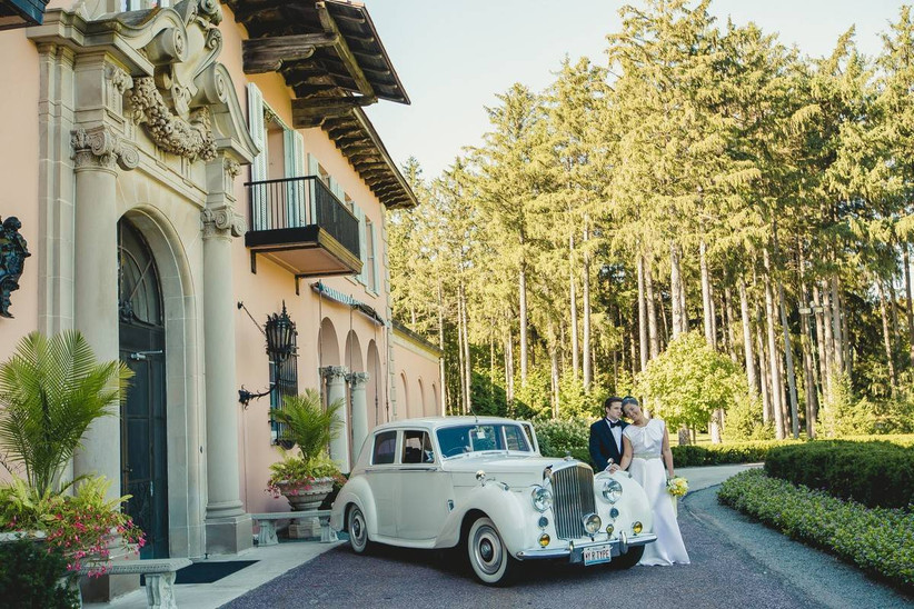 bride and groom stand outside of mansion wedding venue in front of vintage car