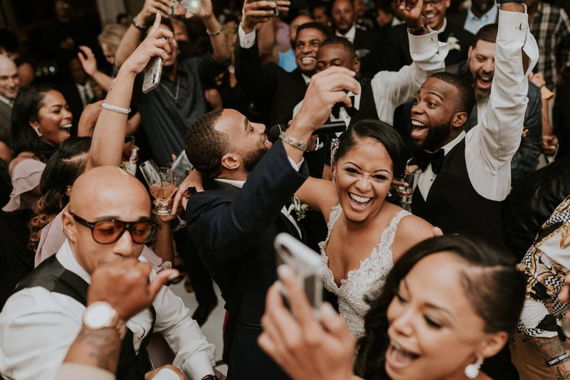 bride and groom are surrounded by smiling guests on the dance floor