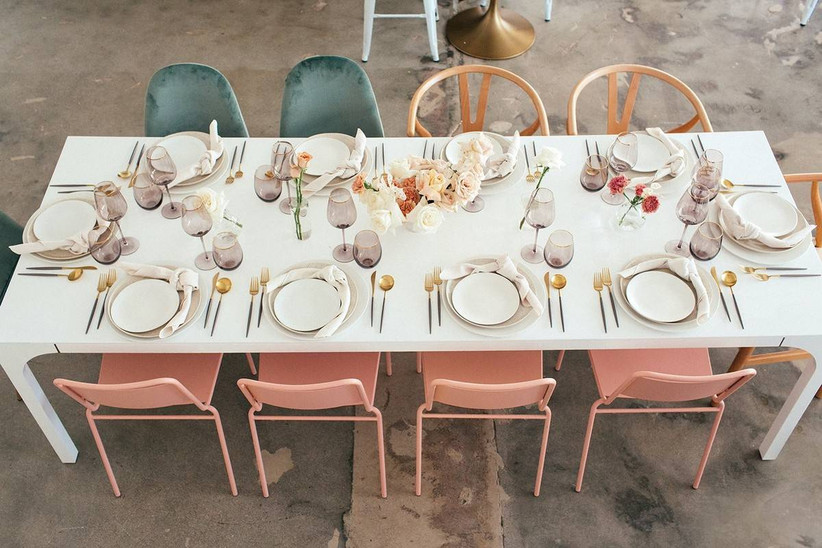 modern wedding reception table with colorful chairs