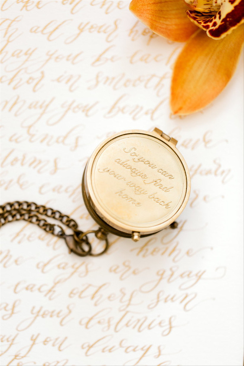 gold compass on a chain engraved with