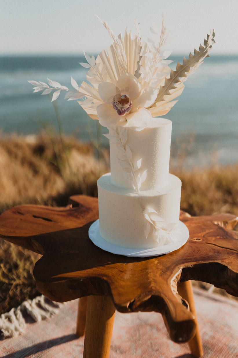 white two-tier wedding cake decorated with neutral wedding flowers including orchid and dried bleached greenery