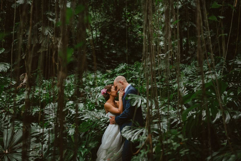 bride and groom kiss in tropical Hawaii forest vines coming down from trees tropical plants surrounding them