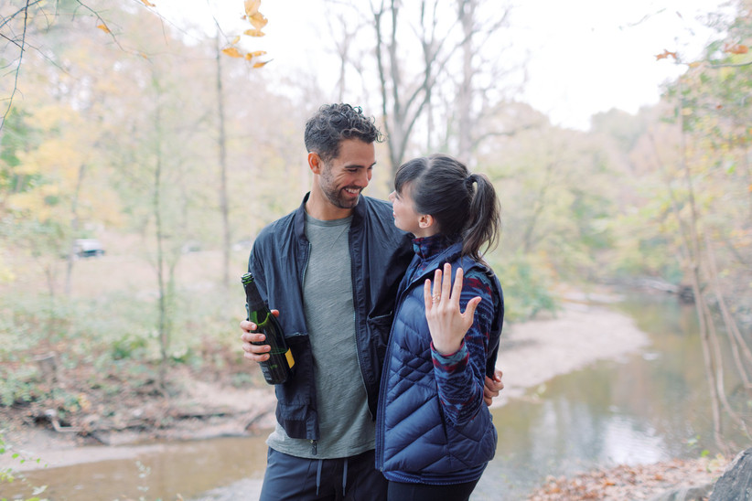 Couple showing off engagement ring and holding champagne after getting engaged