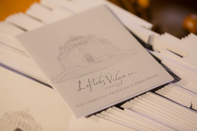 stack of wedding ceremony program booklets with venue illustration and calligraphy on the cover