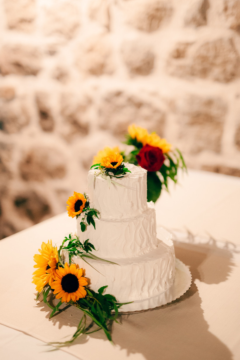 white buttercream wedding cake decorated with yellow sunflowers on each tier