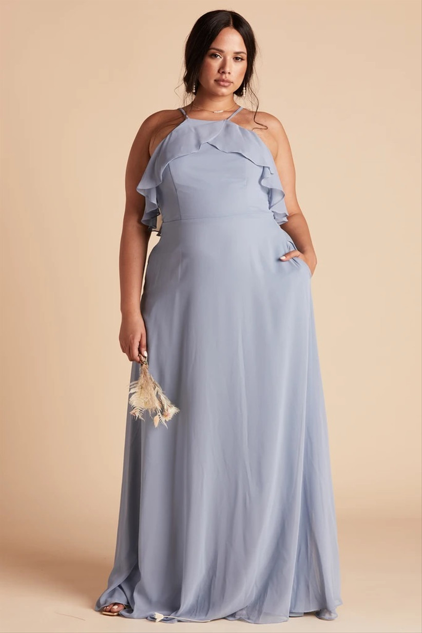 Model wearing lavender pastel bridesmaid dress with pockets and a ruffled neckline