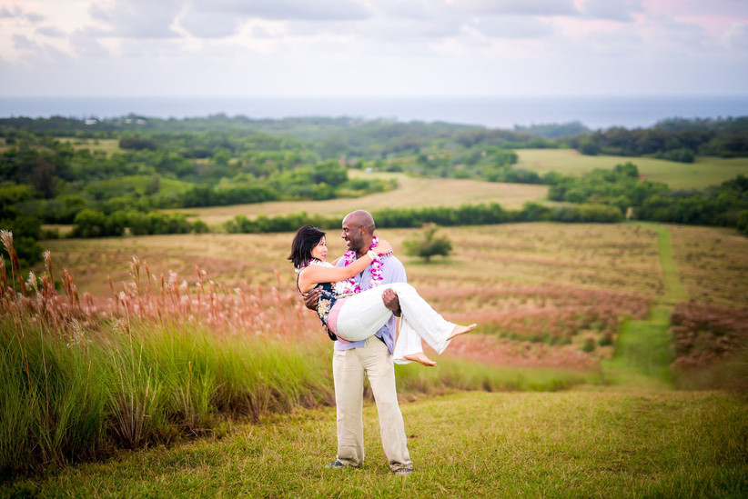 groom carries bride with mountain view in the background