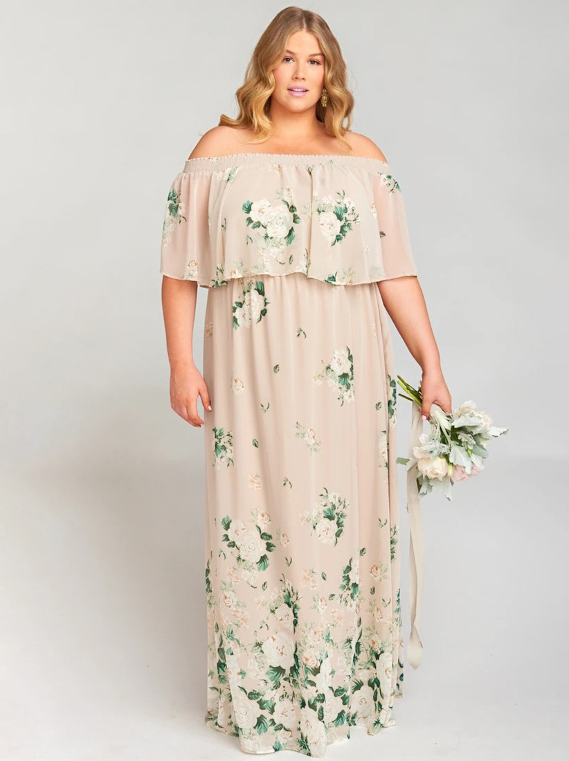 Plus-size model wearing blush pink off-the-shoulder bridesmaid dress with ruffled bodice and white and green florals