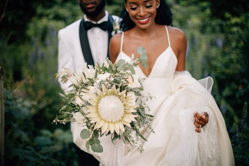couple walking outside bride holding large protea bouquet
