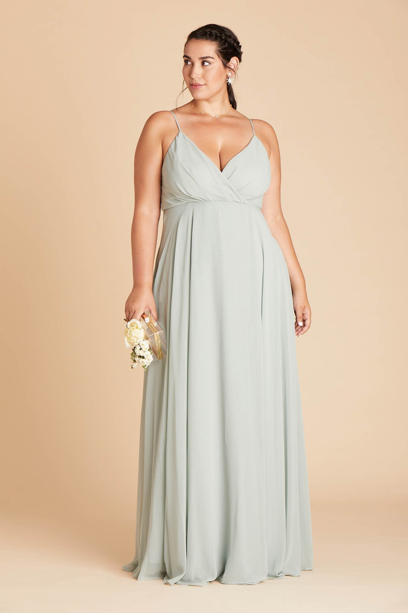 Plus-size model poses while looking off to the side and wearing empire waist trendy bridesmaid dress in mint green color
