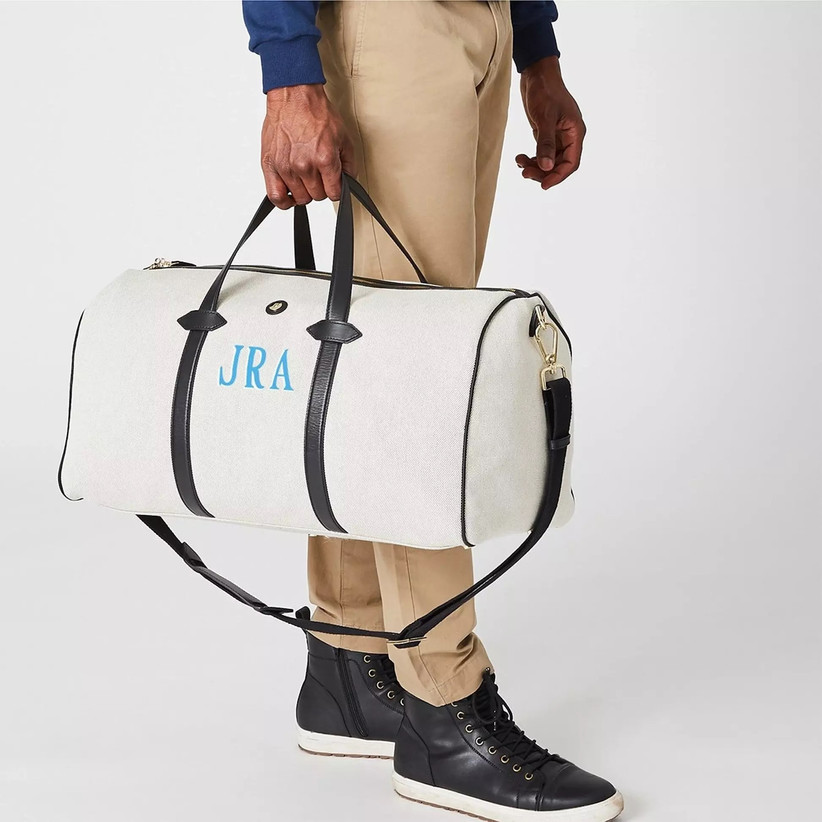 Close up of man holding black and white duffel bag with his initials in blue