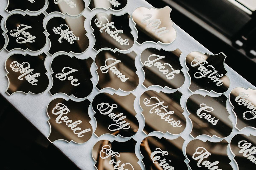 fancy shaped mirrors are decorated with white calligraphy creative celestial wedding theme escort cards