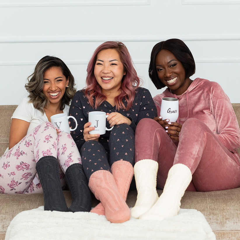Three bridesmaids in cozy pajamas on the sofa wearing matching bridesmaid proposal socks in different shades