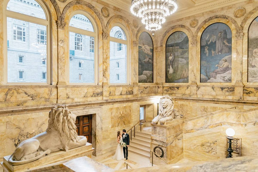 bride and groom stand on the marble staircase next to lion statues at boston public library