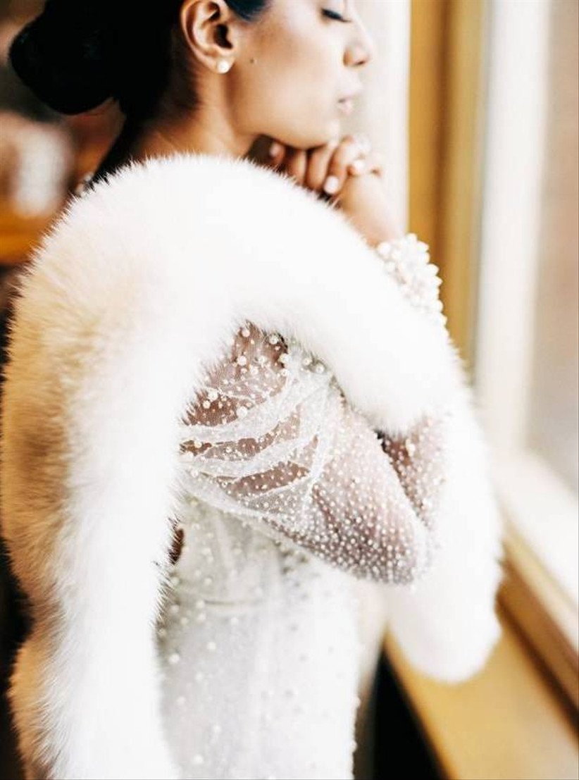 portrait of a bride wearing a beaded wedding dress and white fur shawl