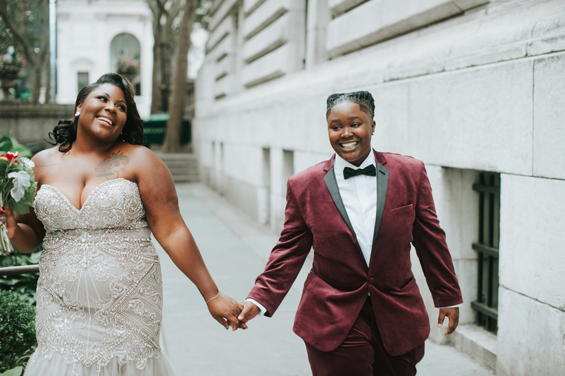 two brides walking down the street holding hands and smiling