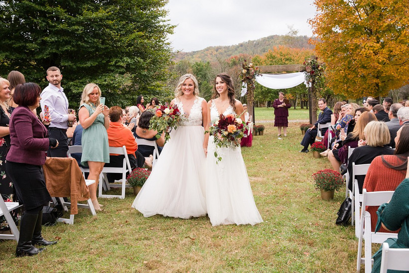 Two brides during recessional at outdoor fall wedding with guests in their seats watching