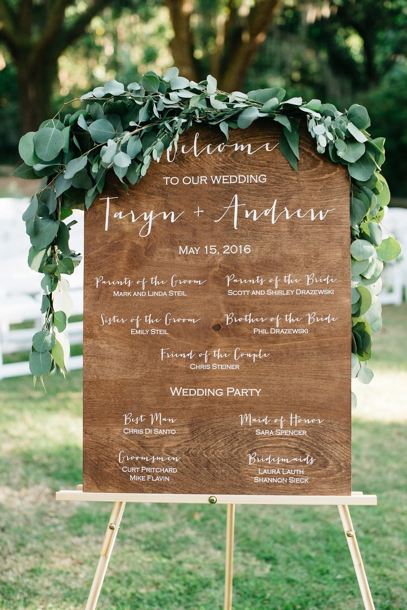 wooden ceremony program sign with calligraphy and greenery displayed on wooden easel
