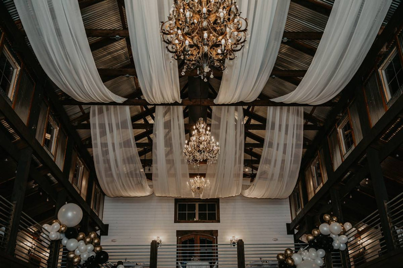 ceiling of wedding barn venue decorated with sheer white fabric swags and gold chandeliers