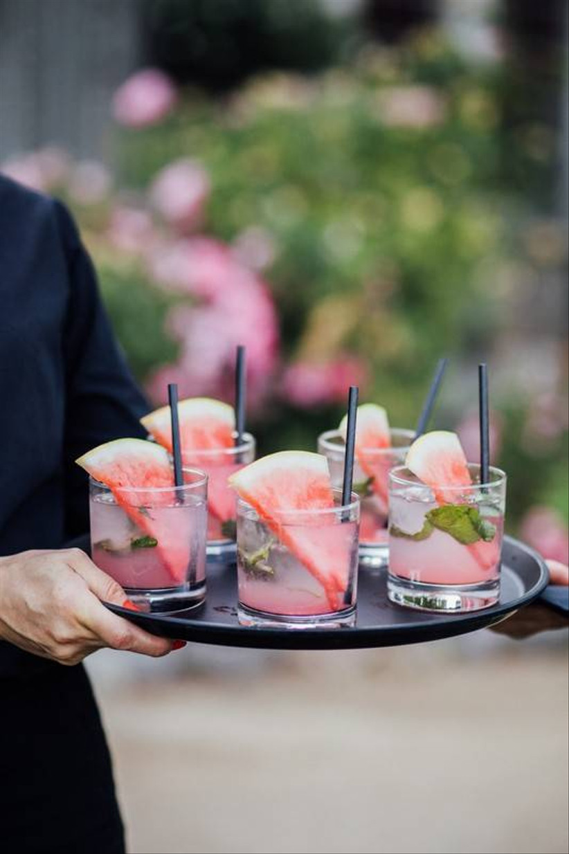 server holding a tray of mojitos with watermelon slices and straws
