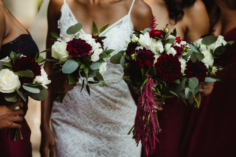 Black bride carries bouquet including burgundy dahlias, red ranunculus, amaranthus, eucalyptus, and other flowers in fall wedding colors
