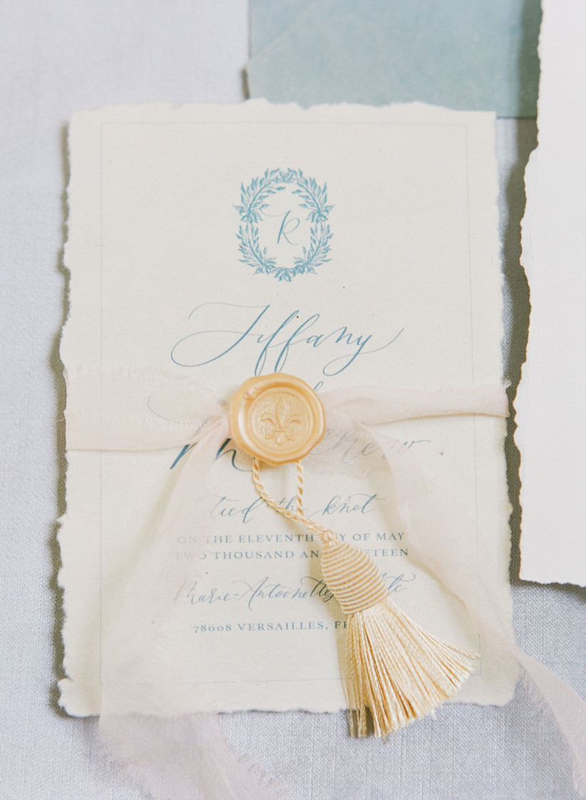 paris themed wedding invitation with blue calligraphy and pale yellow tassel tied around the middle