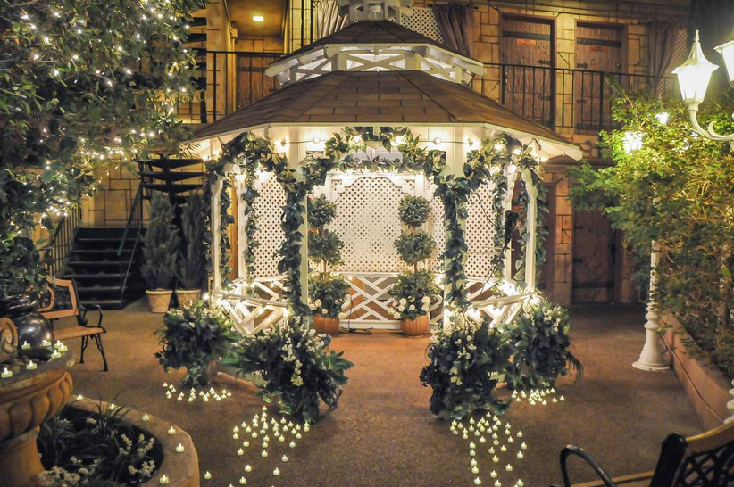 garden-inspired las vegas wedding chapel at night with white gazebo, street lamps, and battery tea lights along the aisle