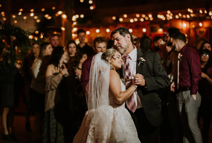 Father daughter dance with guests in background and twinkling lights