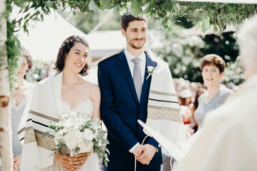 bride and groom stand beneath chuppah wearing prayer shawl