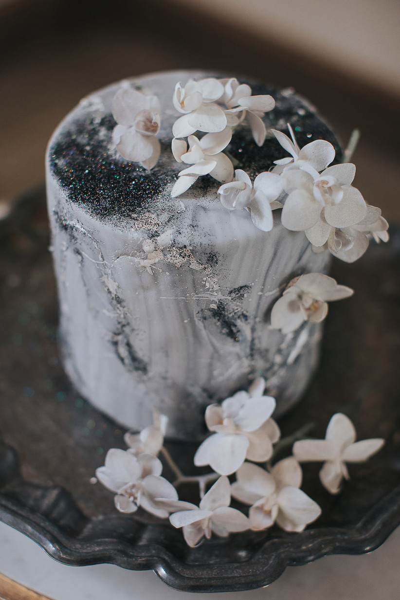 white and gray marbled wedding cake decorated with white flowers and edible silver glitter
