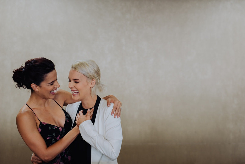 same-sex couple laughs in candid engagement photo