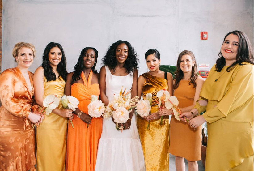 Bride smiling with three bridesmaids either side wearing varying hues of orange and gold