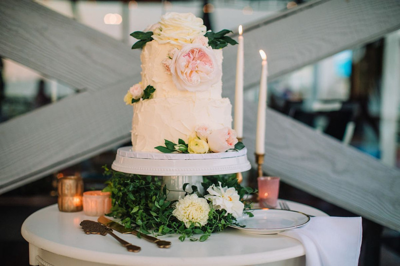 wedding cake displayed on a table with fresh flowers and tall candles