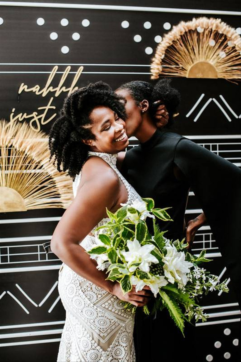 Black same-sex couple bride holds white and green summer wedding bouquet