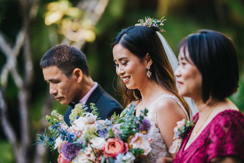 bride walks down the aisle with both of her parents