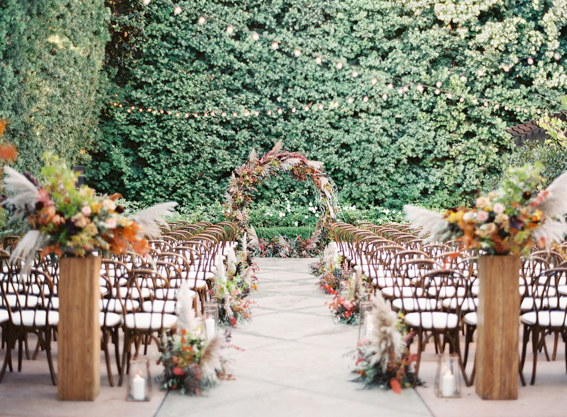 fall wedding ceremony arch with orange and yellow roses